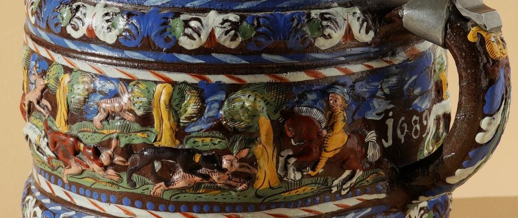 Detail 17th century Creussen saltglazed stoneware tankard with hunting scenes